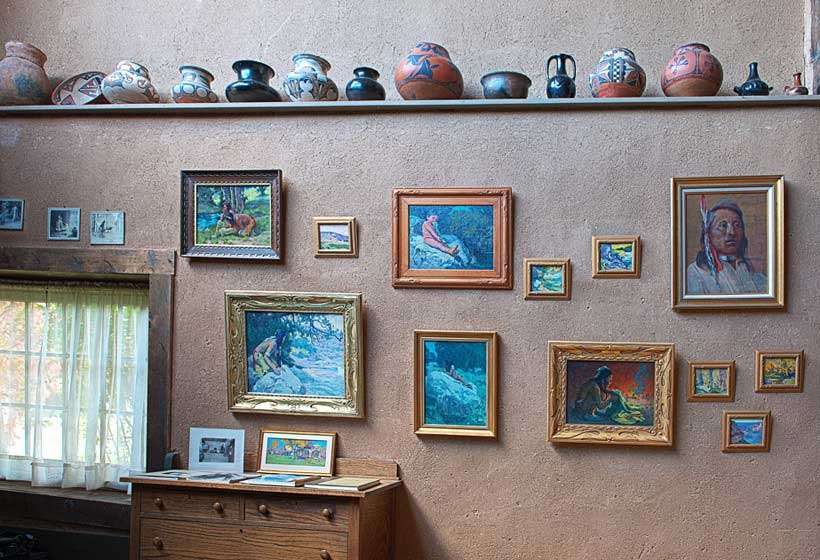East wall of Couse's studio showing his paintings and Native American pottery.